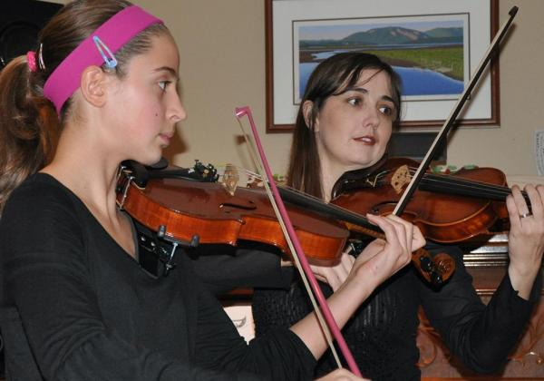 Young teen in a hot pink headband playing a violin duet with Rhiannon