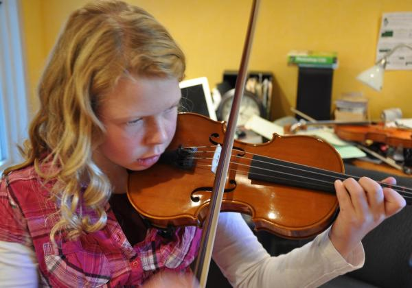 Little blonde girl intensely focused on playing violin in 3rd position