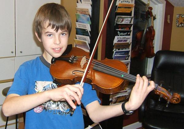 Preteen boy playing violin and smiling at the camera