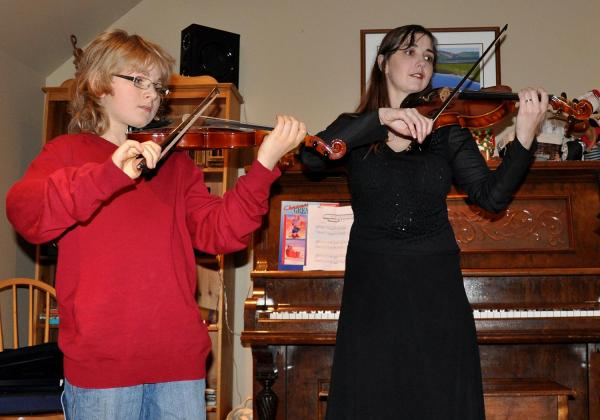 Young teen boy in a red sweater playing a violin duet with Rhiannon, clad in formal black