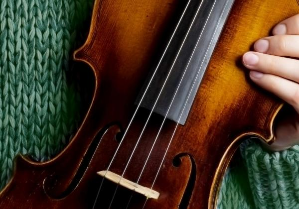 Person in green sweater holding violin