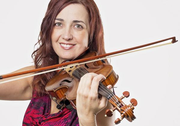Rhiannon playing violin and smiling at camera
