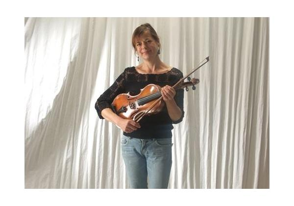 Woman in black shirt and jeans holding a Violin with a white draped background