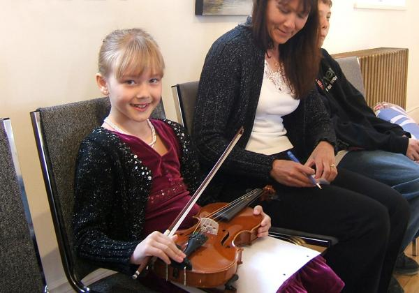 Adorable blonde girl holding a violin on her lap as her mother smiles at her