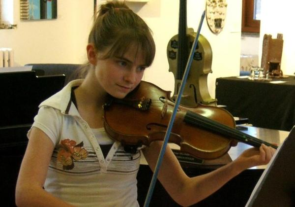 Young teen playing violin in front of a golden violin trophy