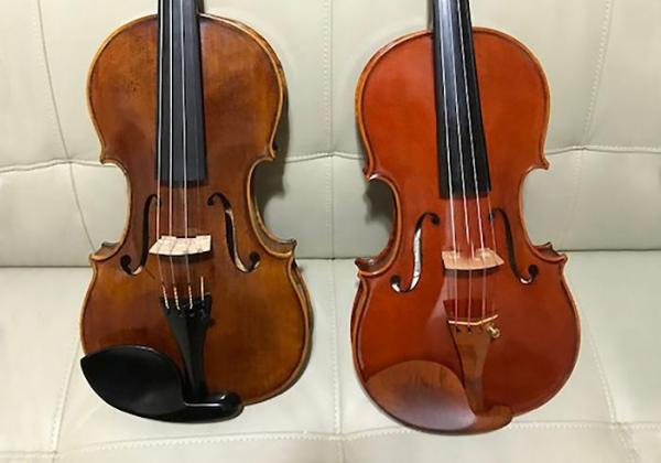 A Migiel and Dimitrov violin sit side by side on a leather couch