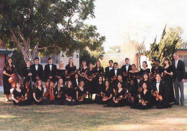 High school orchestra standing outside, with the teacher and Rhiannon on the far right