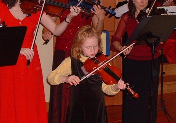 Cute little redheaded girl playing a violin with adults playing behind her