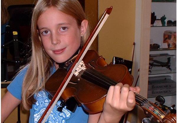 Blonde teen girl playing violin smirks at the camera