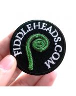 Fingers holding a detailed Fiddleheads.com Embroidered Iron-On Patch