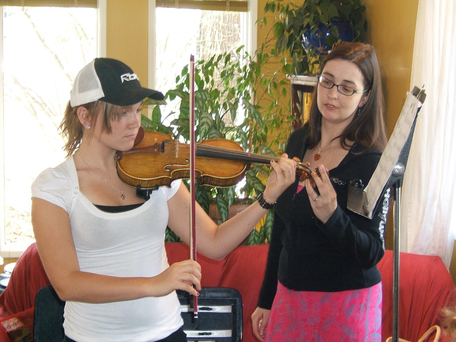 Rhiannon assisting a teenaged girl playing a violin