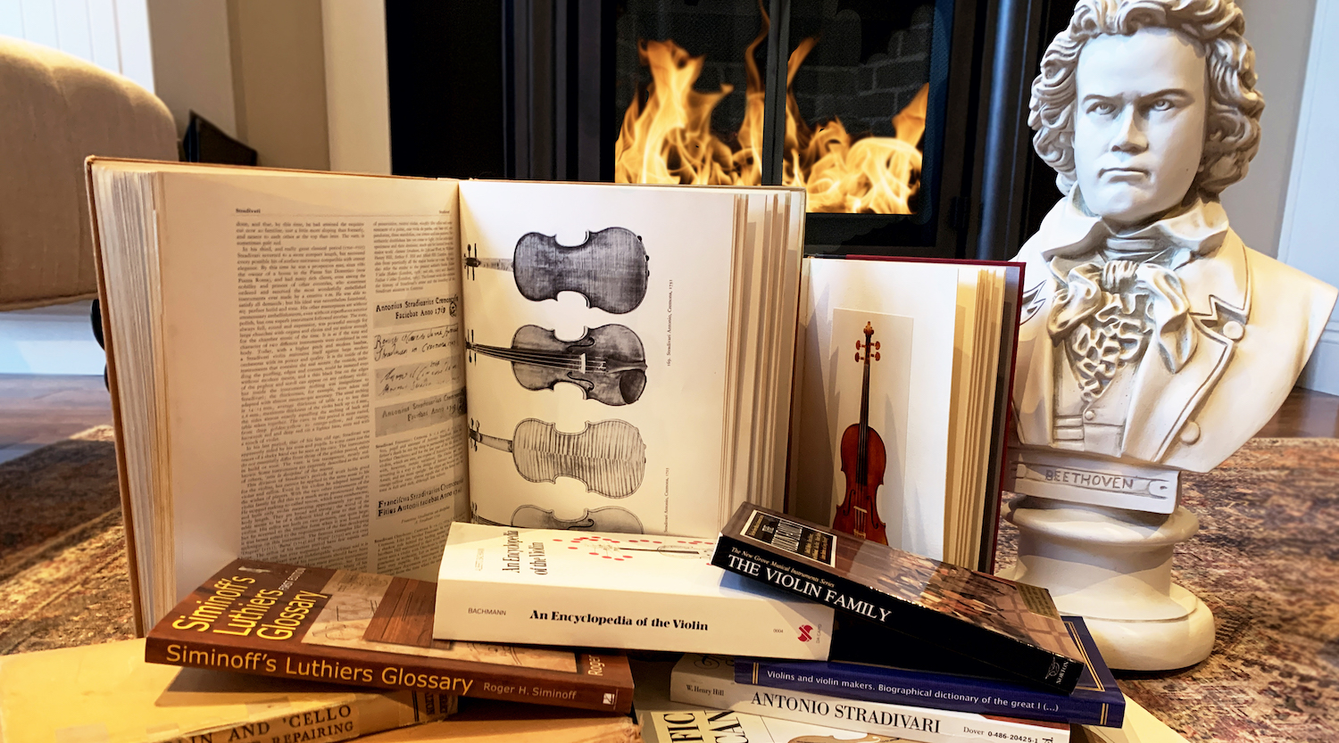 Stacks of violin encyclopedias and books with a Beethoven bust in front of a fireplace