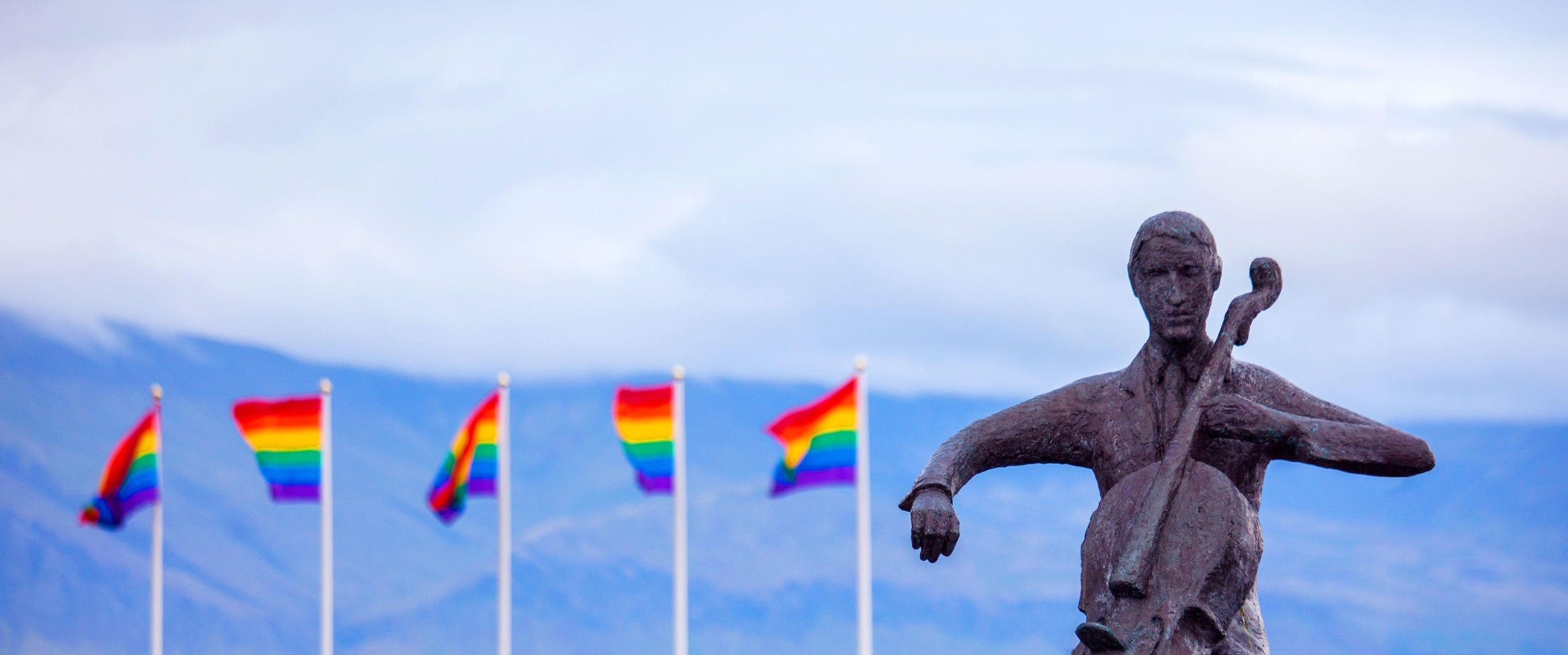 pride flags behind statue of a cellist
