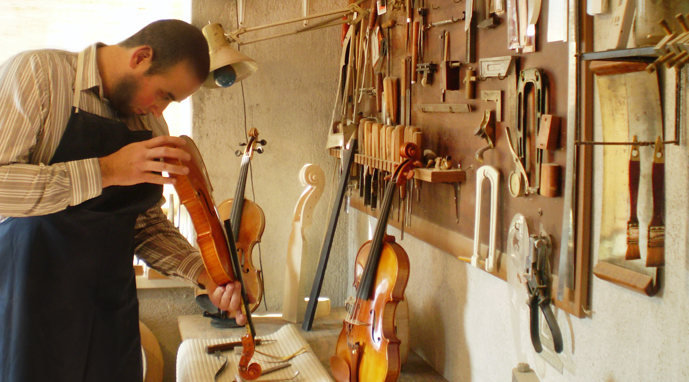 luthier at his bench in his workshop inspecting a violin