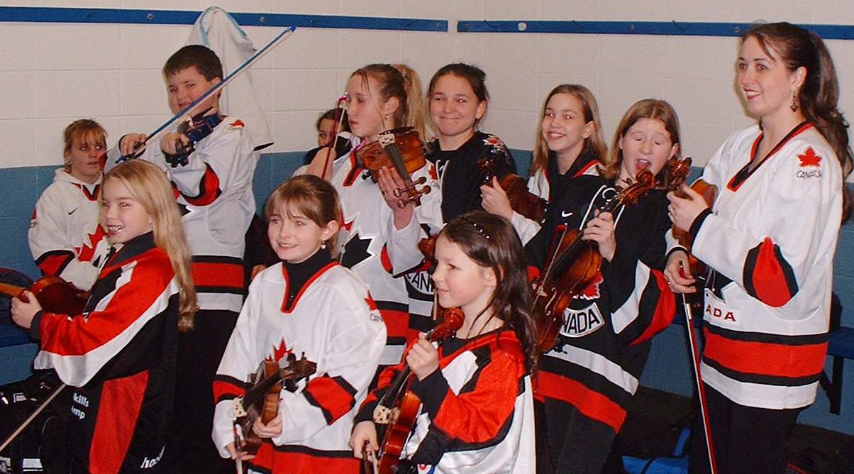 Rhiannon and her students play violin in hockey jerseys