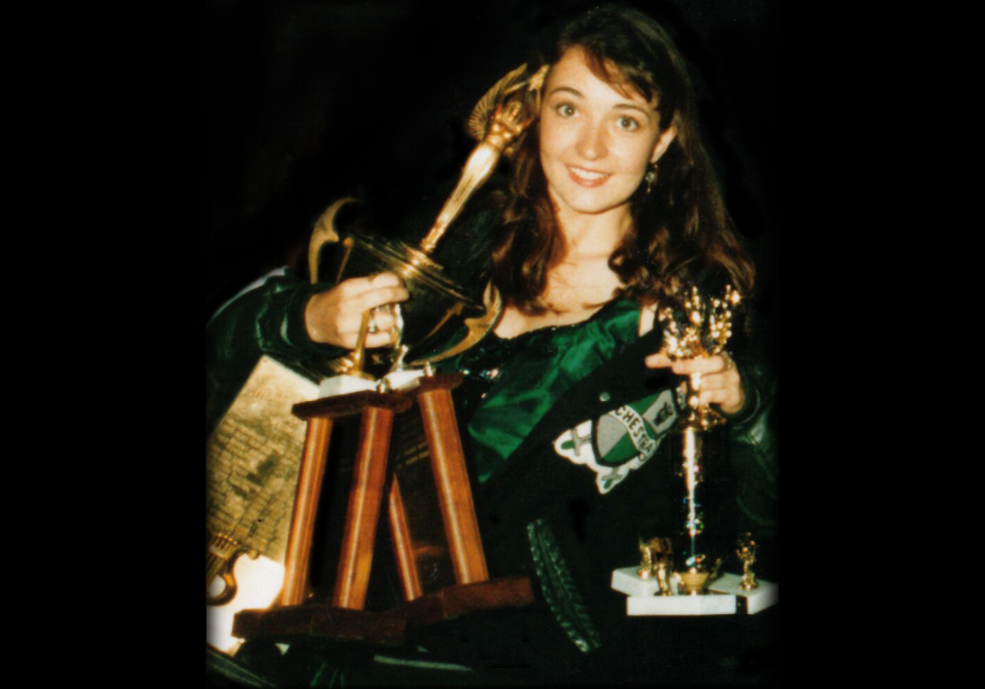 Rhiannon, in a green formal dress and letterman's jacket, smiling and balancing a stack of six brass trophies