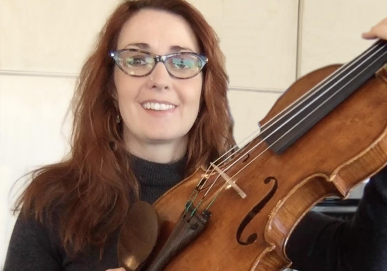 Rhiannon Nachbaur holding up a Violin to the camera