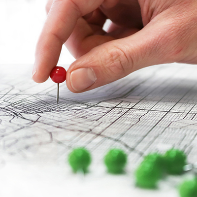 hand moving a red push pin in a map closer to a group of green pins