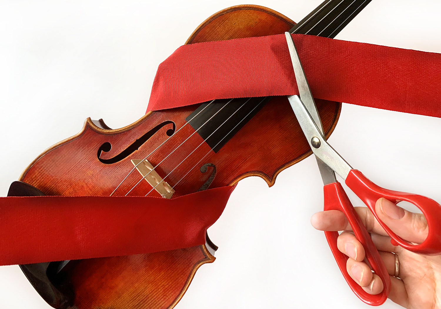 Hand with red handled scissors cutting a red ribbon wrapped around a violin