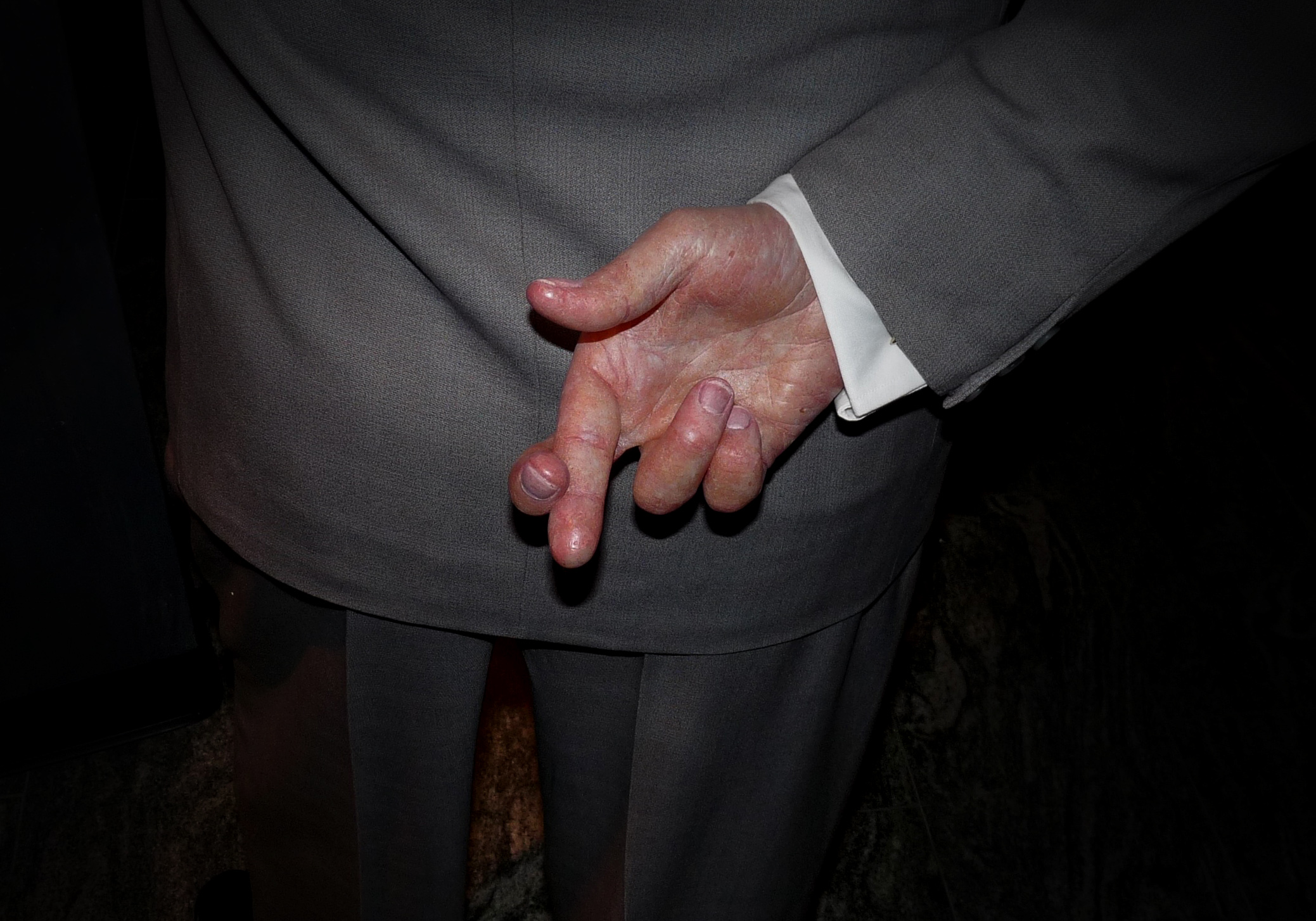 suited old man in shadows crosses his fingers behind his back