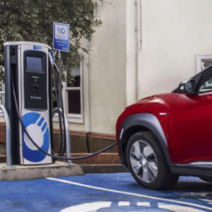 Red Hyundai Kona electric car parked and charging