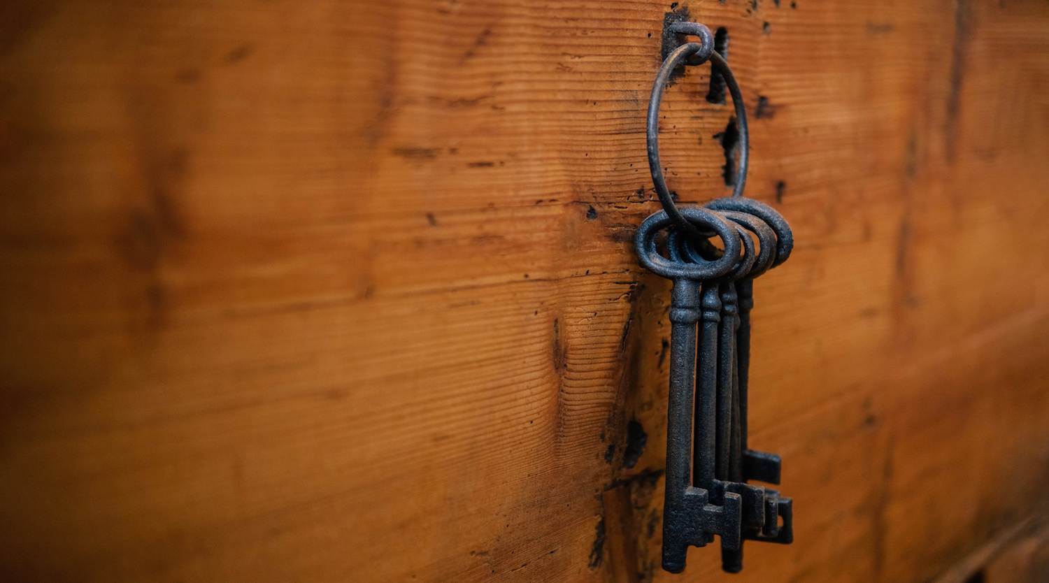 antique keys hanging on hook on wooden wall