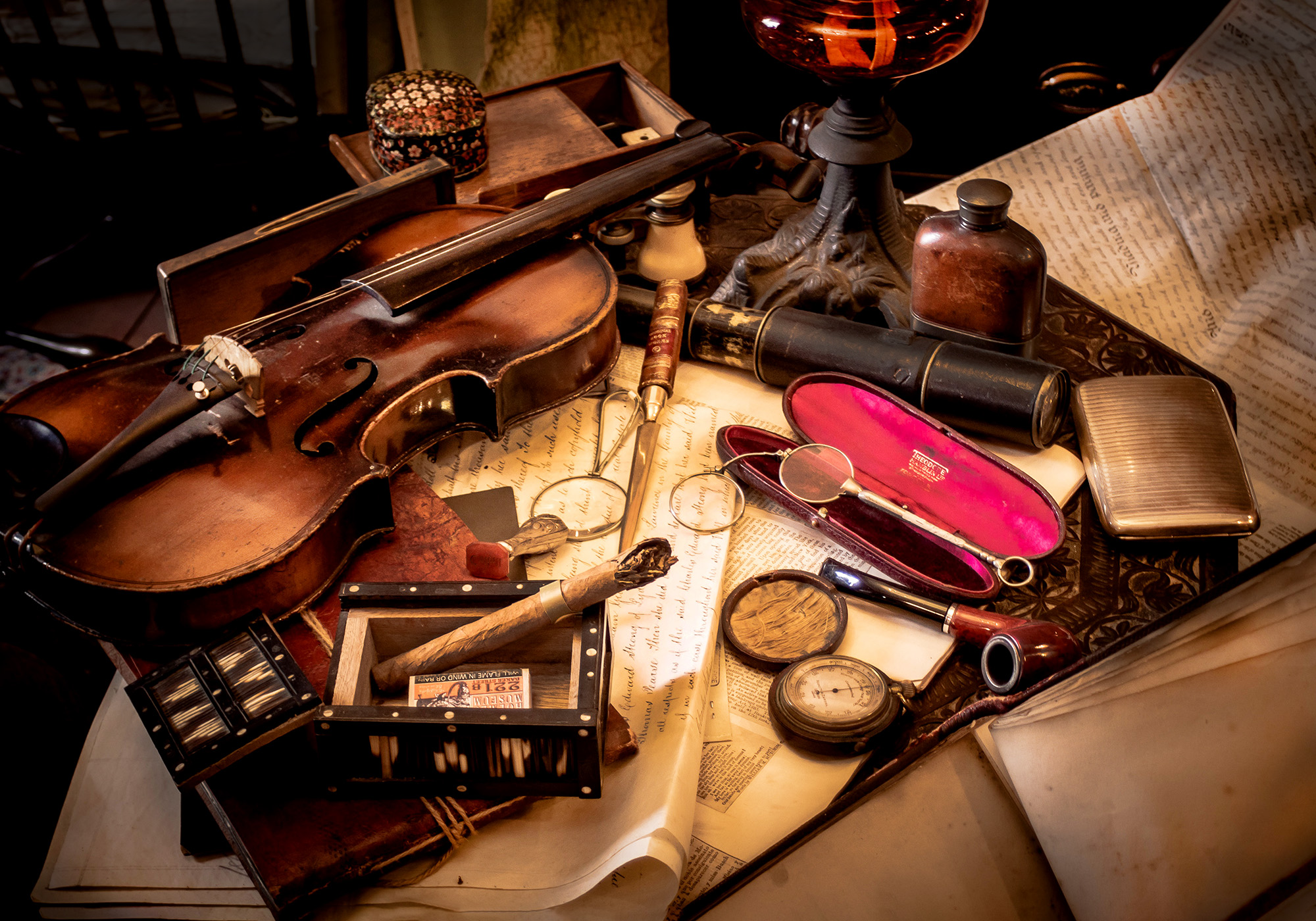 old violin on a desk with many exotic antiques and trinkets