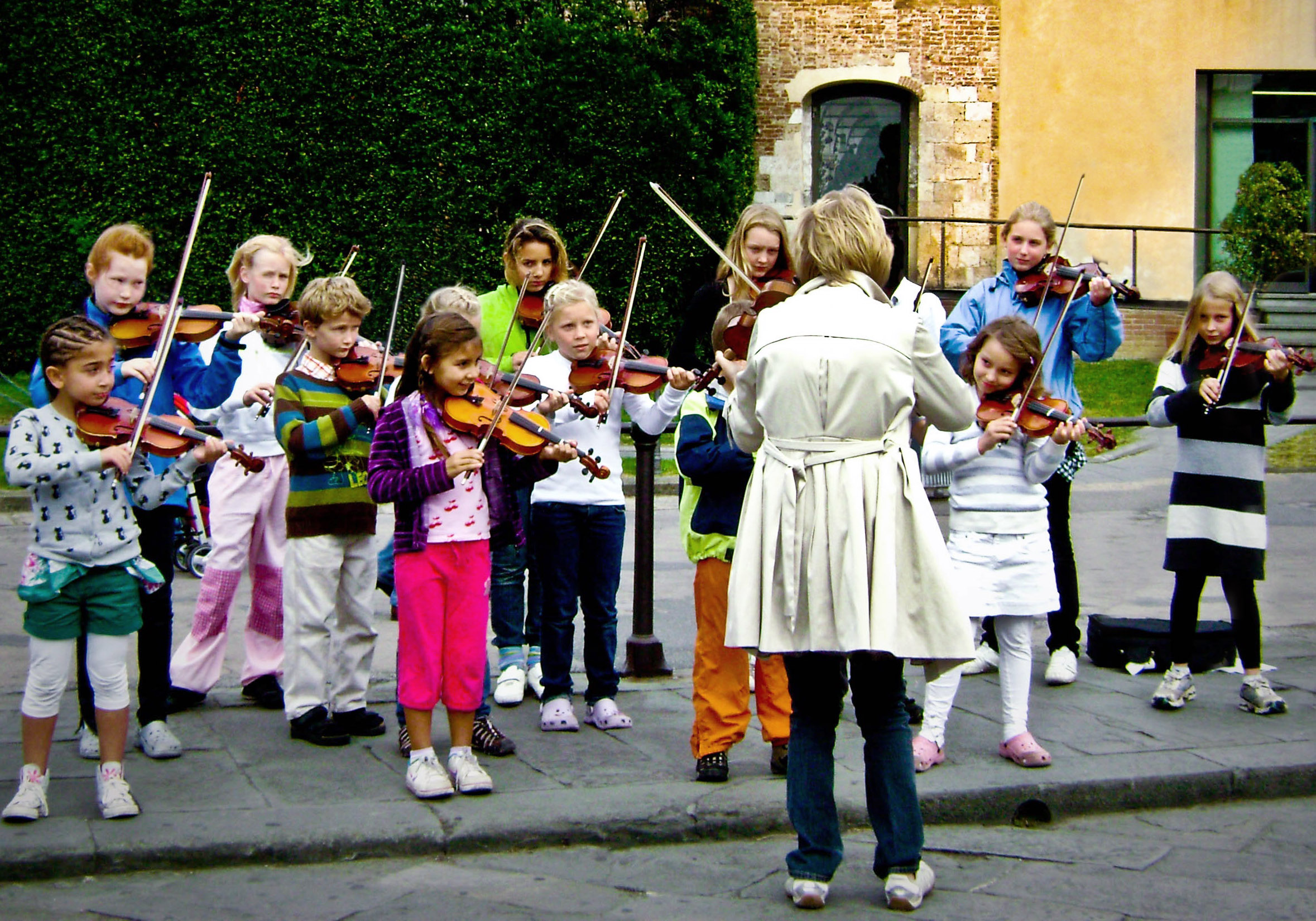 Teacher and a group of children of many ages all playing violin in front of an old brick building