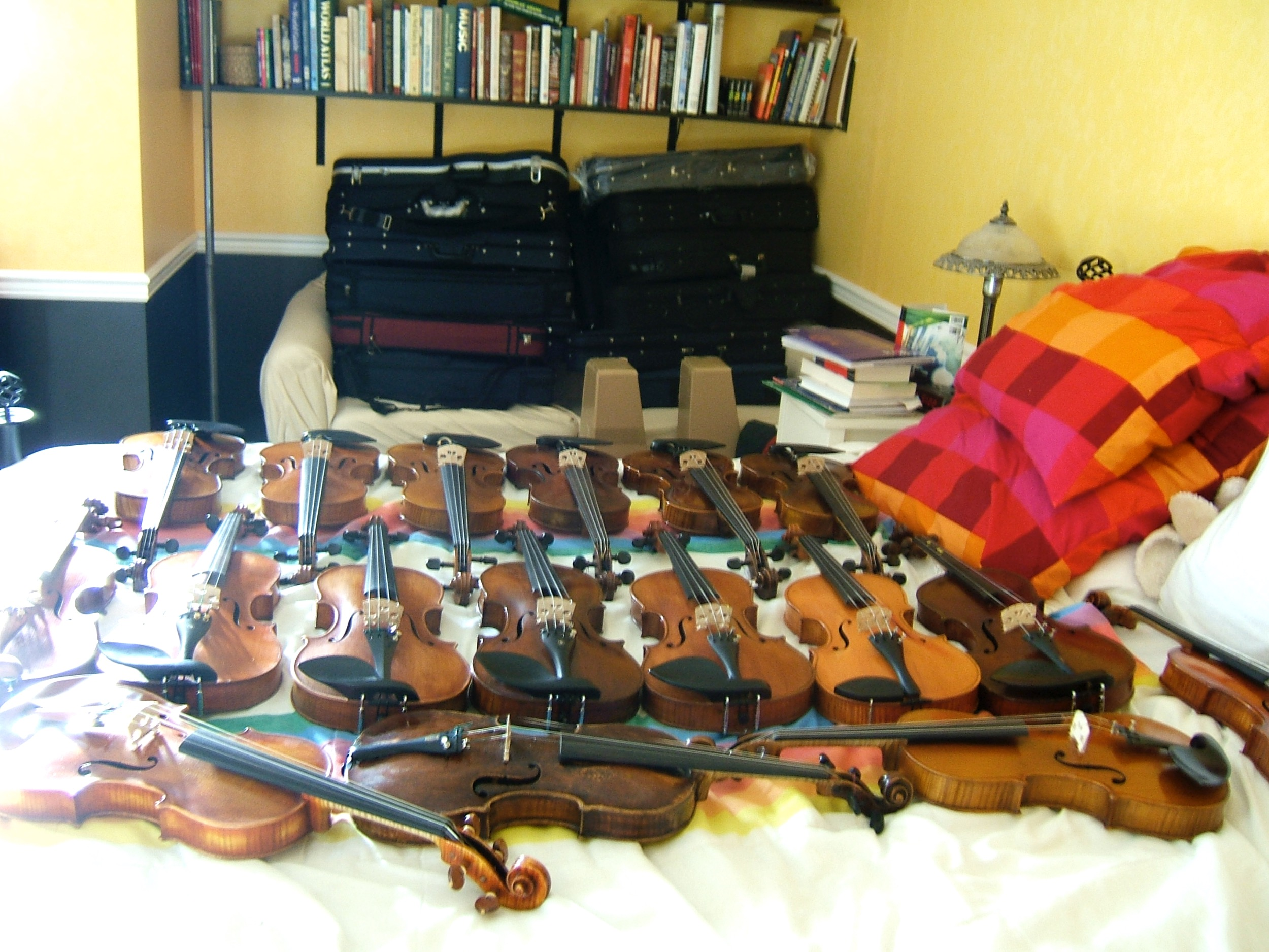 Violins and cases laid out over a bed and couch, taking up every inch of space