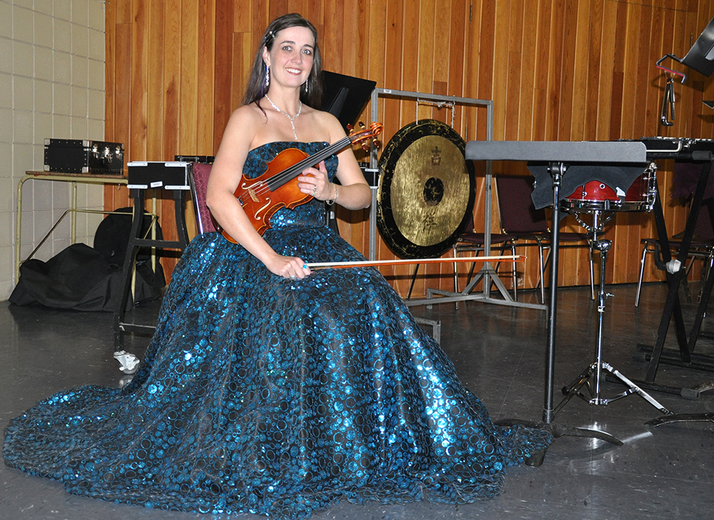 Rhiannon wearing a sequinned teal ballgown and holding a handmade Zhu violin on the symphony stage