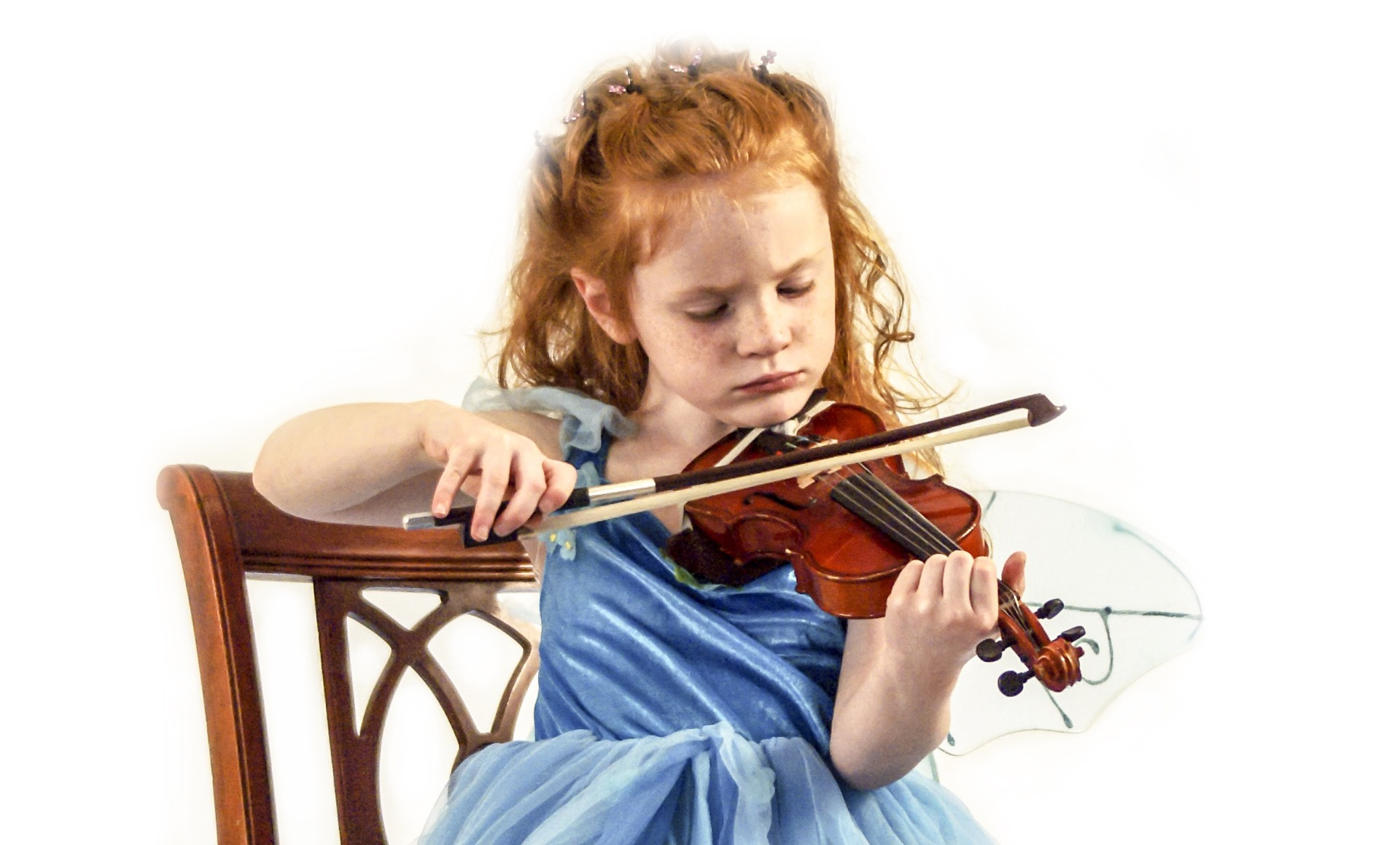 little redheaded girl in a blue fairy costume playing violin