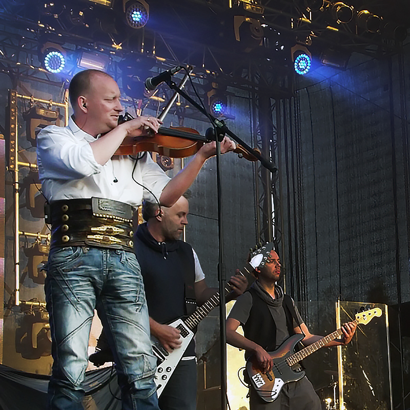 Topa playing his violin on a lighted stage with other band members
