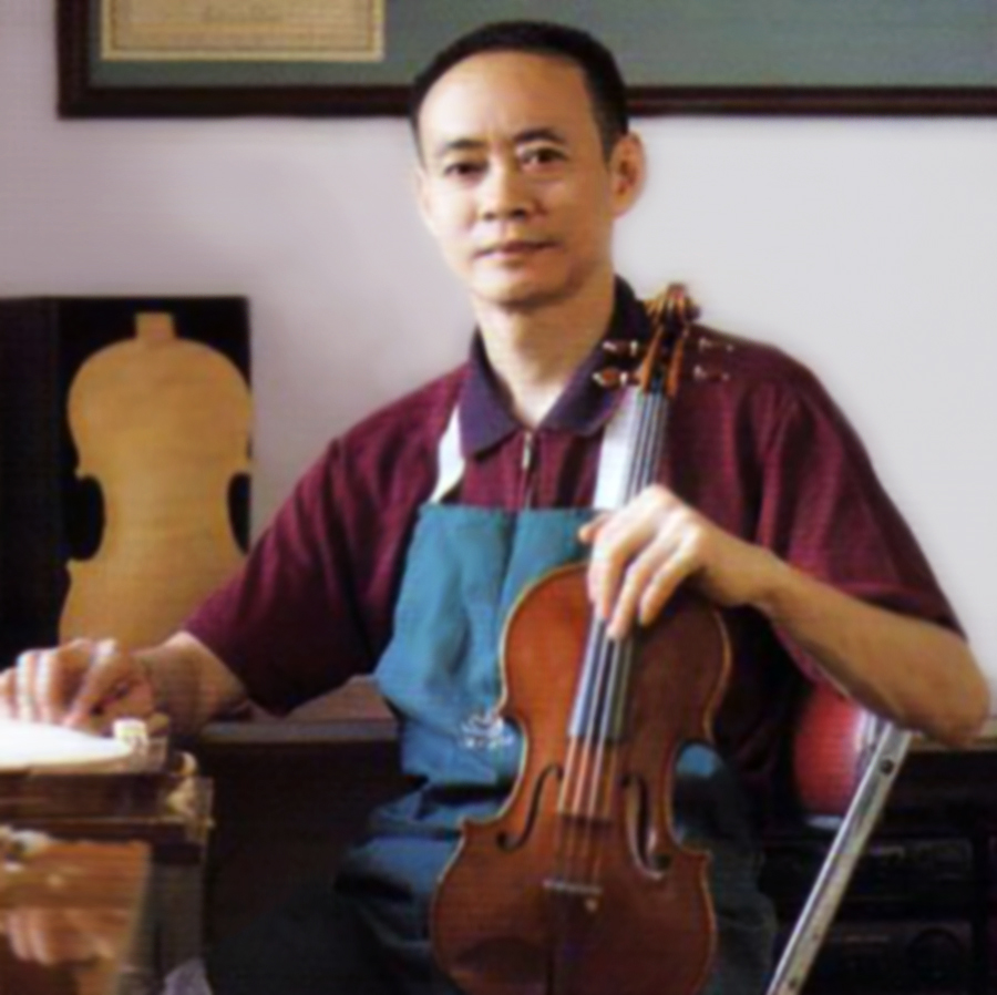The late Mr. Zhu holding a violin in his studio
